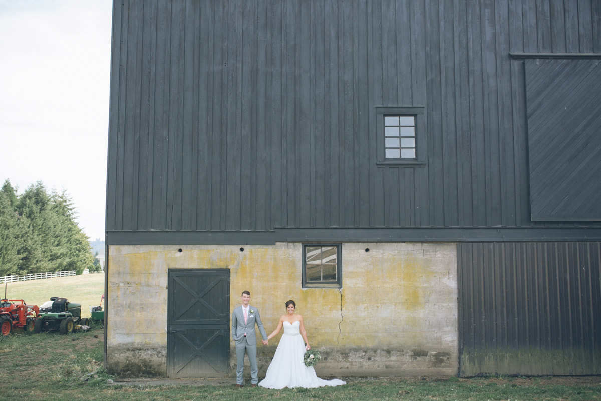 bride and groom pose in front of barn