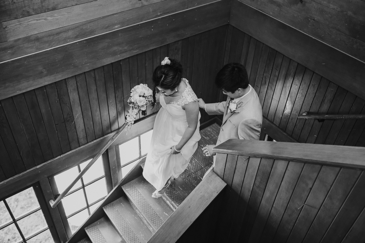 bride and groom walk down staircase