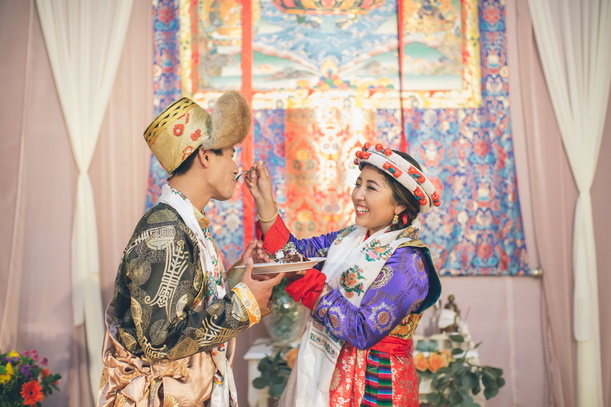 traditional tibetan bride feeding cake to groom