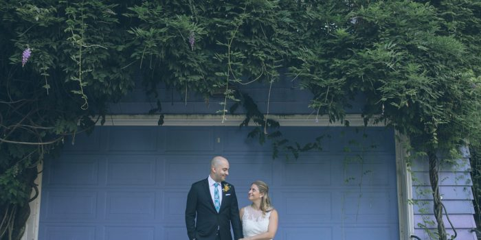 bride and groom standing in front of blue wall