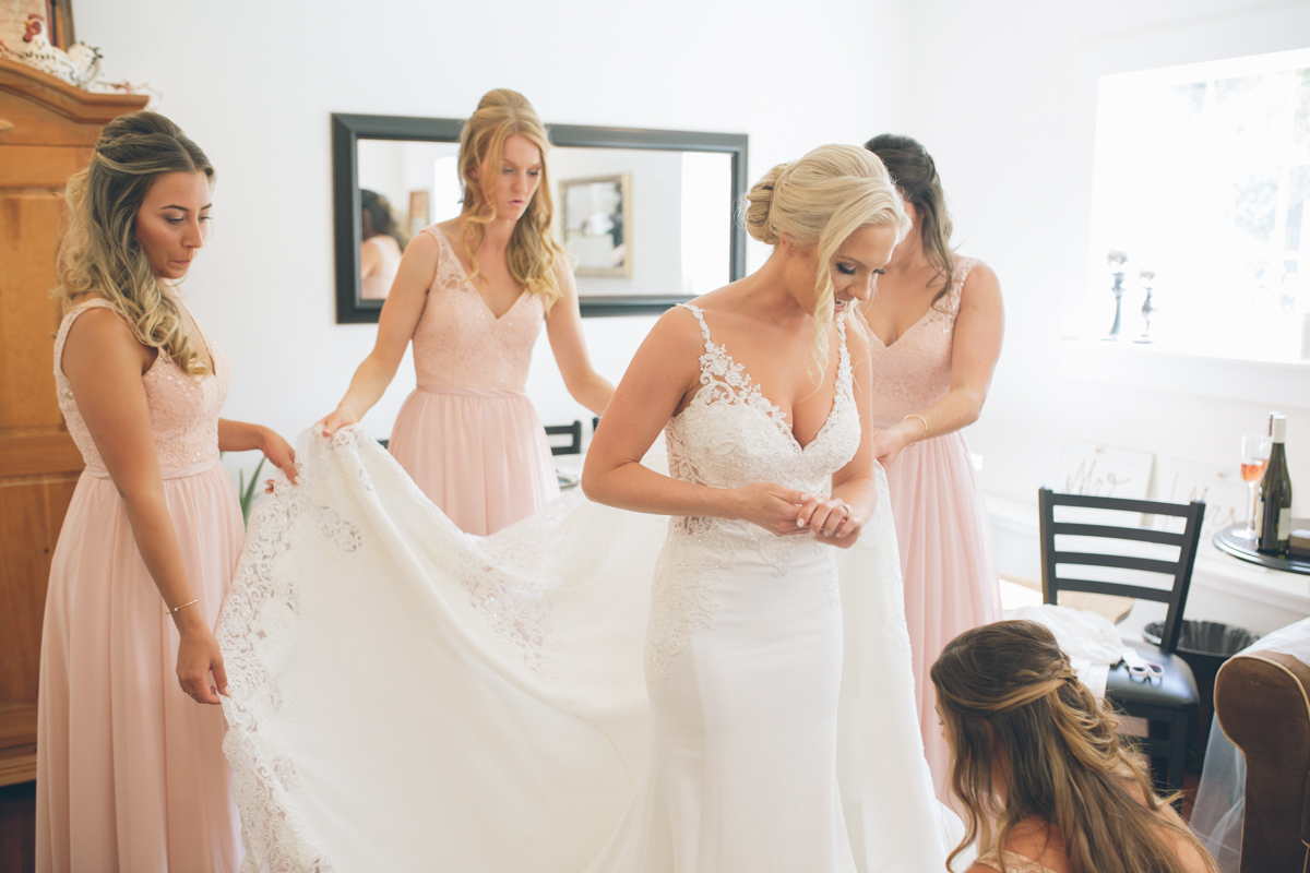 beautiful blonde bride getting ready with bridesmaids