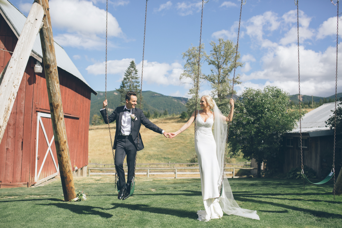 fun photo of bride and groom posing on swings
