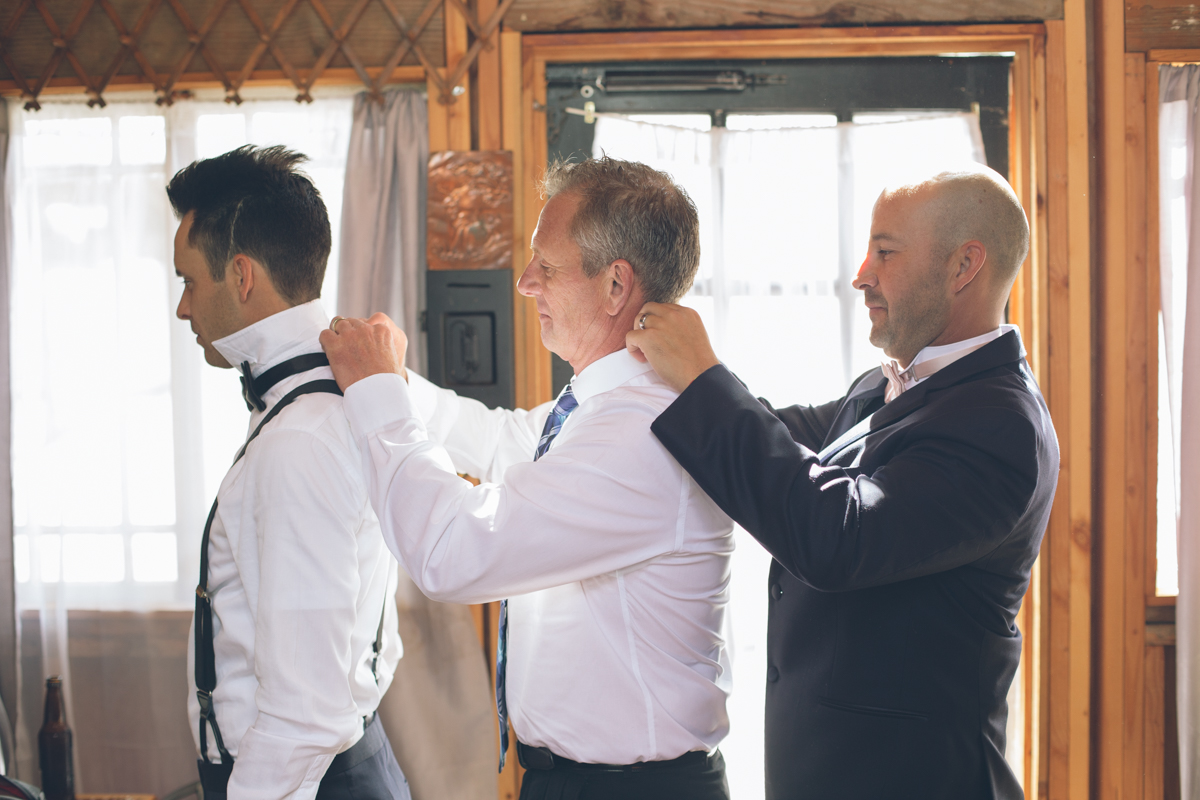 best man helping groom getting ready