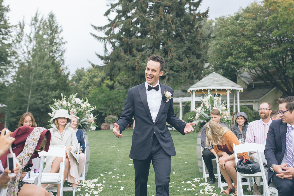 smiling groom walks down aisle in the rain