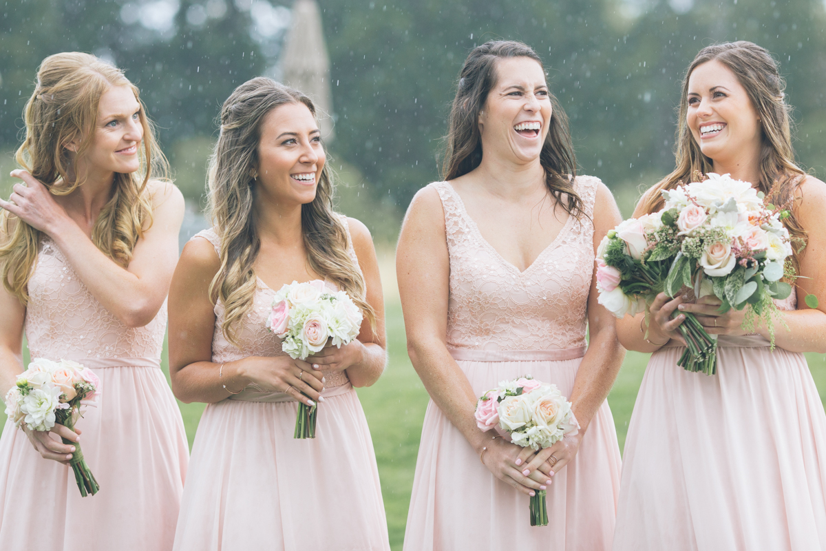 laughing bridesmaids at rainy wedding ceremony oregon