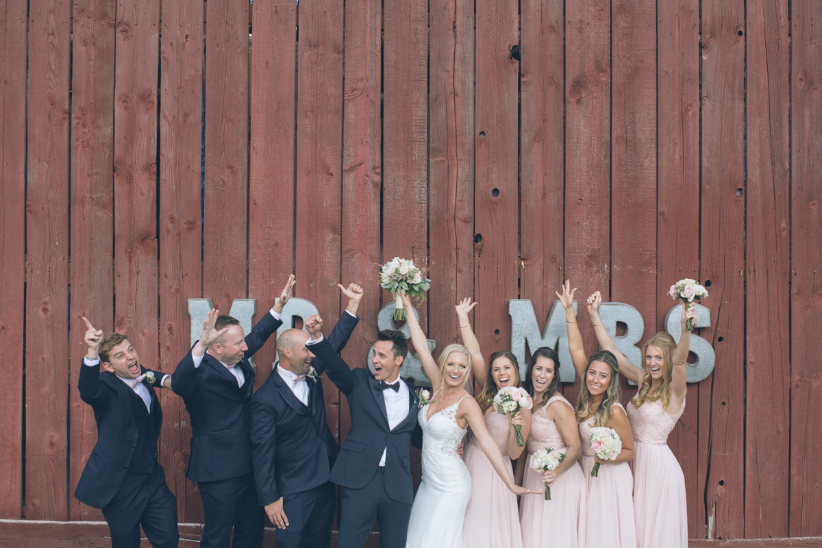bride and groom having fun with bridal party