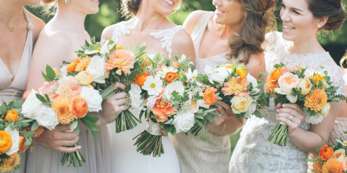 bride and bridesmaids holding orange wedding bouquets