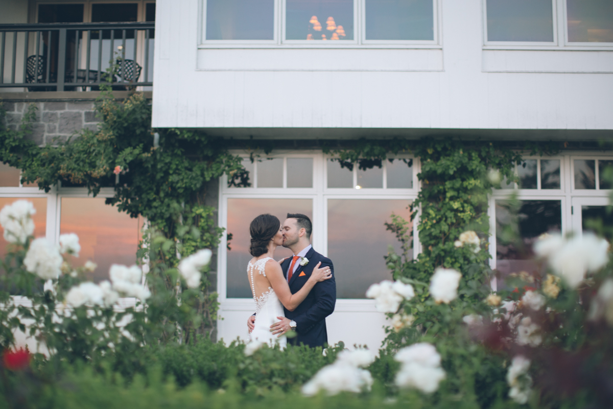 bride and groom kissing in window