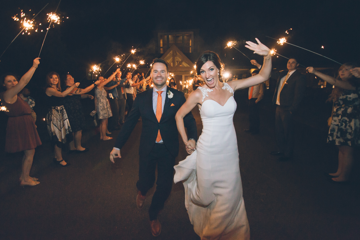 bride and groom run through sparklers exit