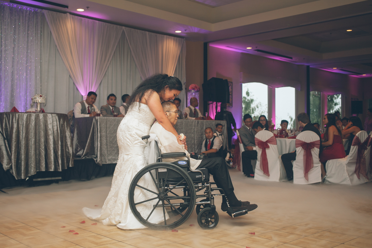 daughter dancing with father in wheelchair