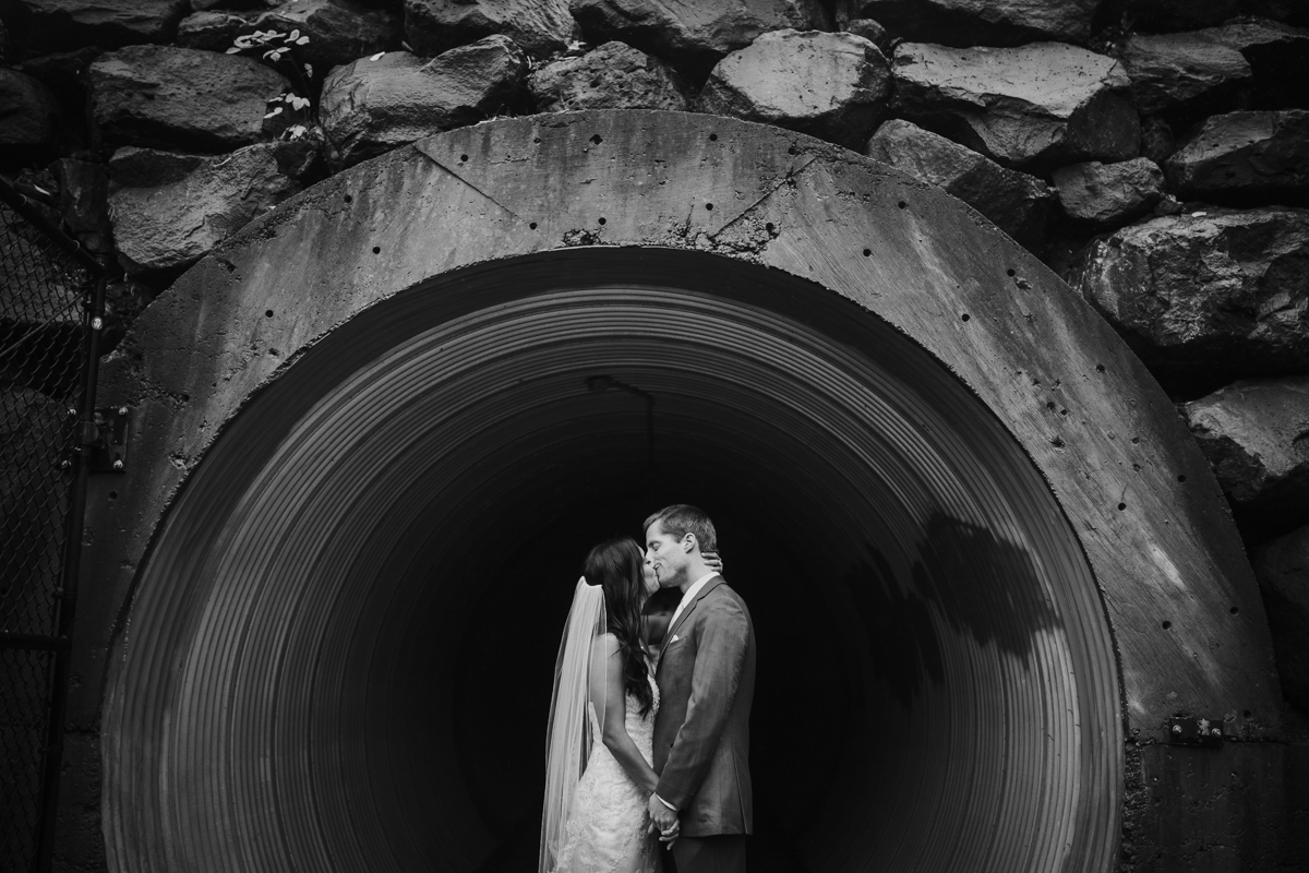 bride and groom taking photos in tunnel
