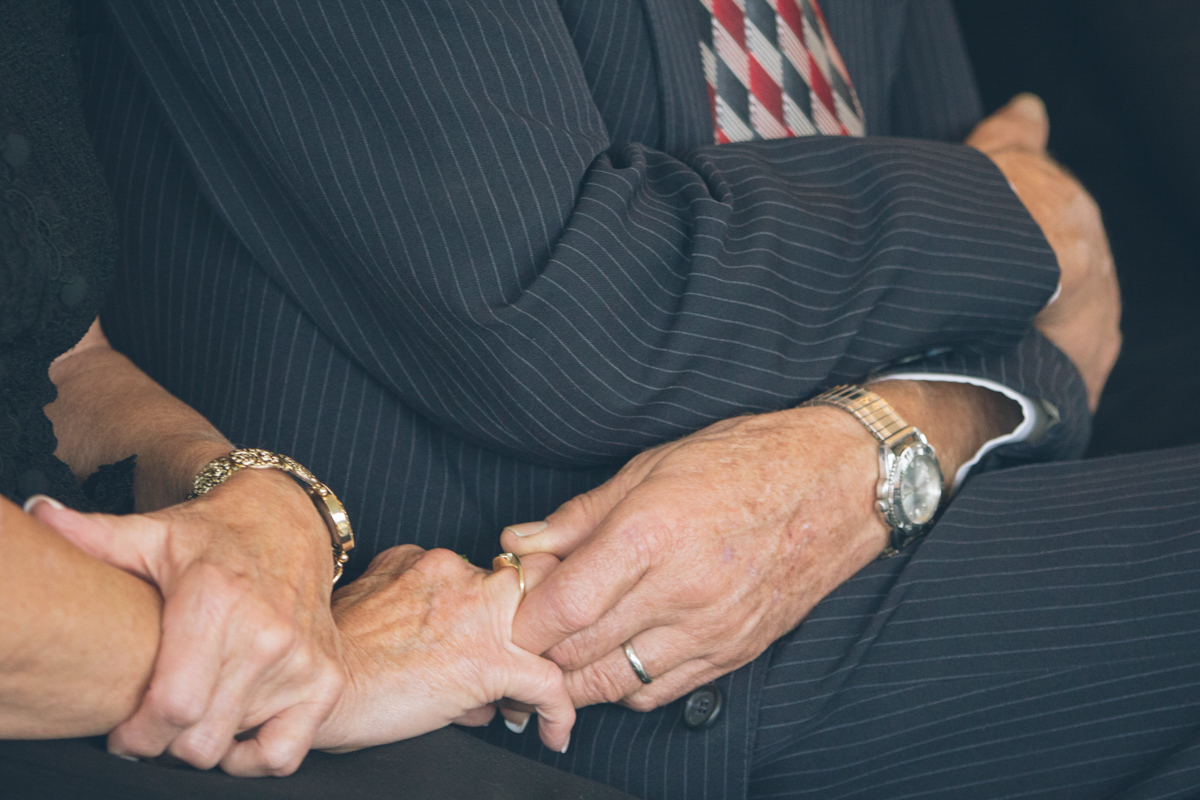 closeup of parents holdings hands during wedding ceremony