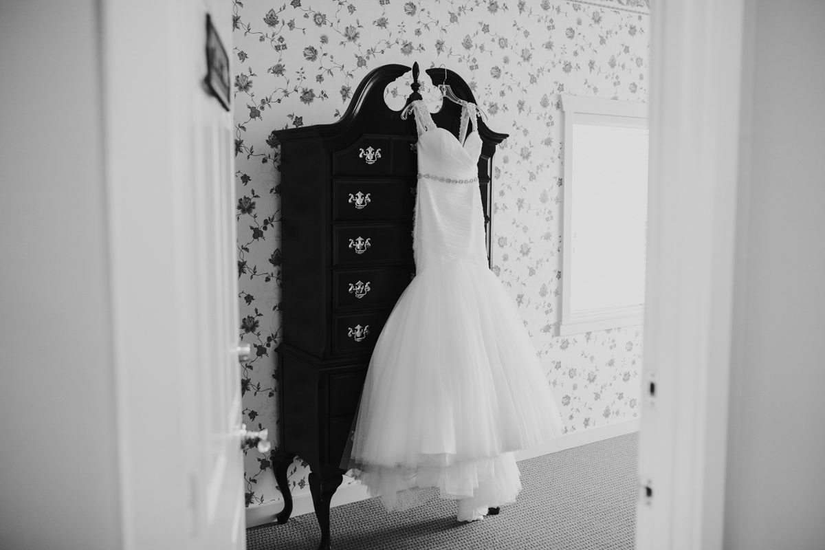 wedding gown hanging on armoire