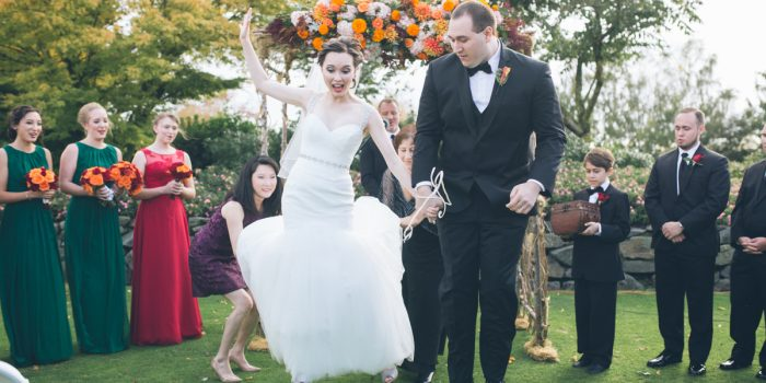 bride and groom jump over broom at wedding ceremony