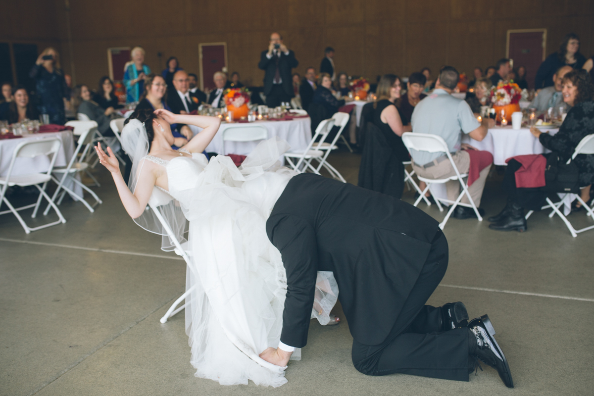 groom bites off garter at wedding