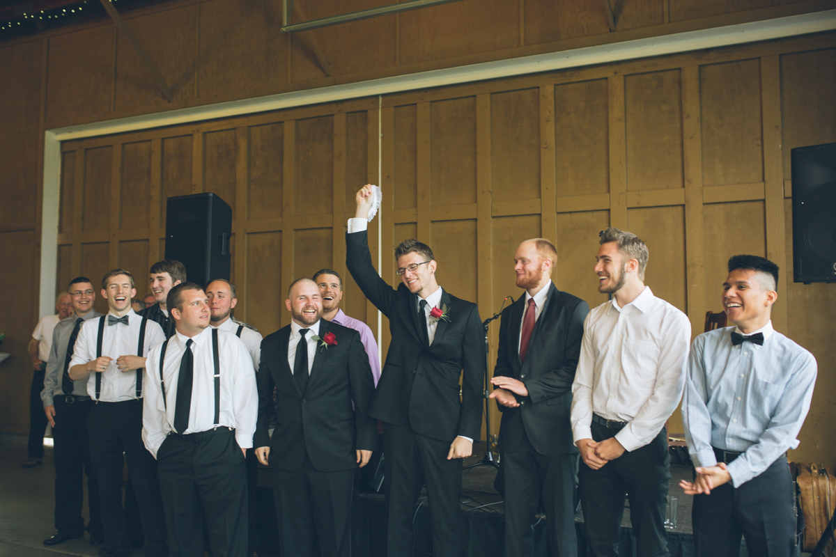 groomsmen catch garter at wedding reception