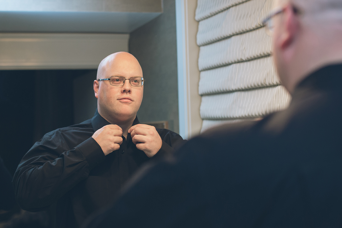 groom getting ready in mirror