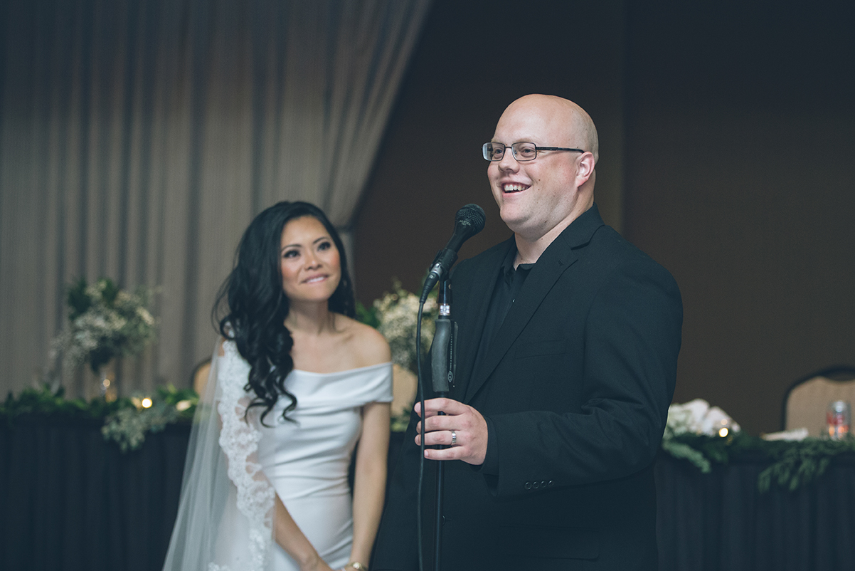bride smiles as groom gives speech