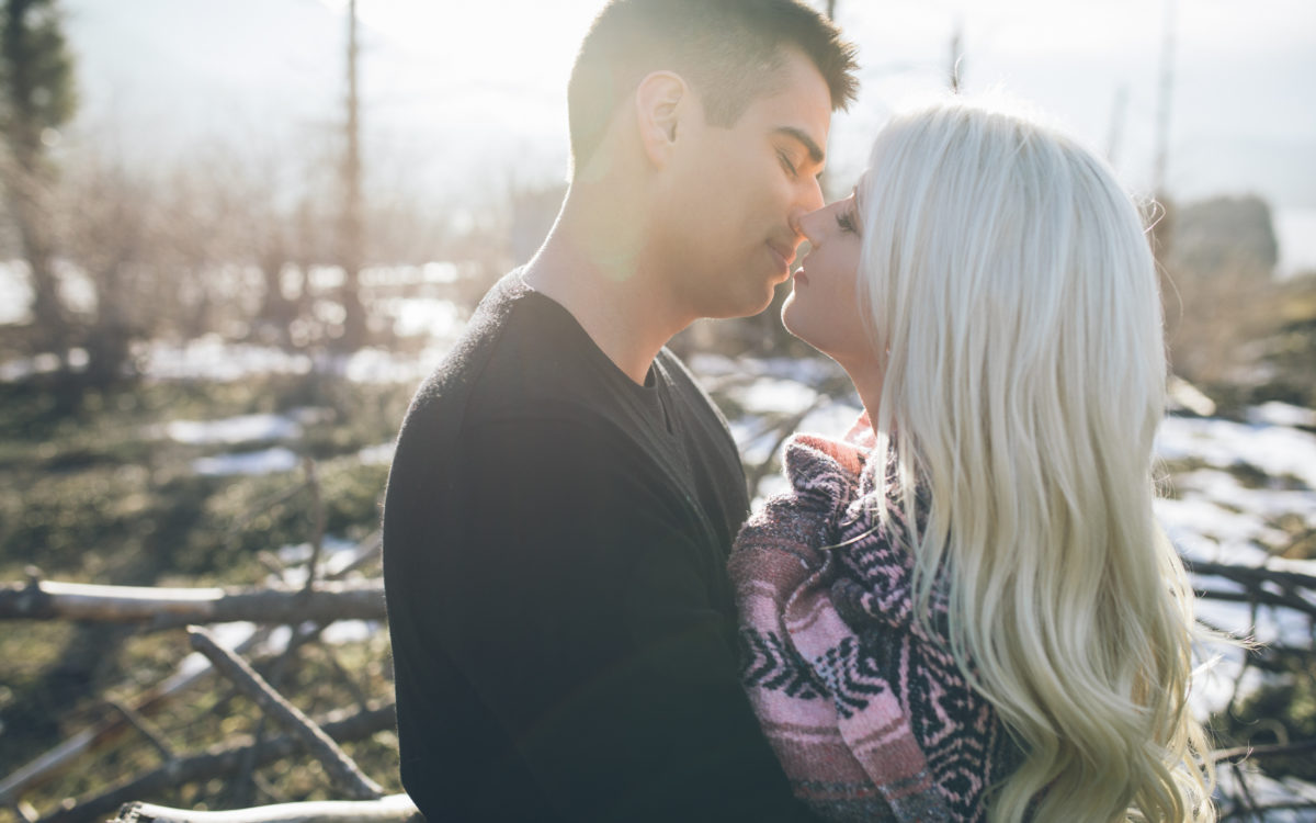closeup of man kissing woman snow engagement pics